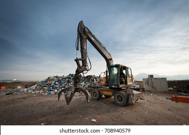 Bulldozer with mechanical arm grabbing waste from a pile at city landfill. Waste management, ecology concept.