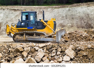 The bulldozer moves and spreads the soil and rubble on the embankment of the road. Work bulldozer on the construction of a highway.. Road under construction.
