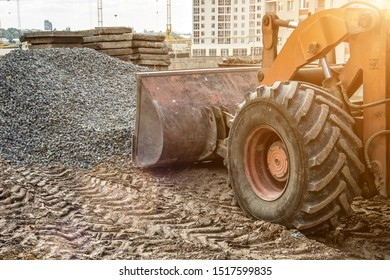The bulldozer moves and spreads the soil and rubble on the embankment of the road.Bulldozer working on Dirt in the Construction Site.Road under construction.