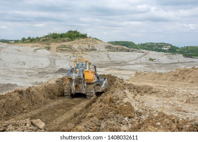 Bulldozer moving marl and limestone over the quarry edge