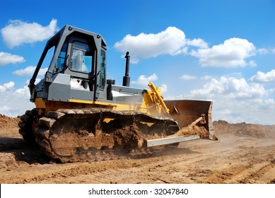bulldozer moving on earth with raised blade against blue cloudy sky