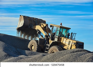 Bulldozer in the process. Extraction of gravel and sand. Minerals.