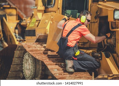 Bulldozer Professional Mechanic. Caucasian Technician Taking Machine Under Maintenance. Construction Heavy Duty Equipment.