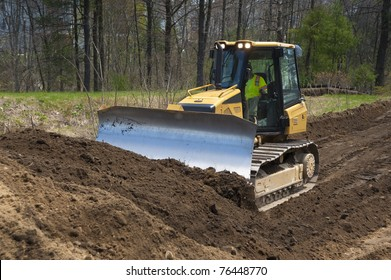 Bulldozer pushing dirt on construction site near a big airport