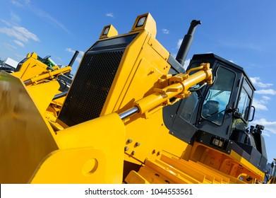 Bulldozer, Reihe von riesigen gelben, leistungsstarken Baumaschinen mit großen Spuren und Spuren, Schwerindustrie, Bodenansicht, blauer Himmel und weiße Wolken auf Hintergrund