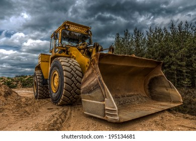 a bulldozer in a sandpit with a dark cloudy sky in the background