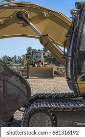 A bulldozer is seen through a backhoe.