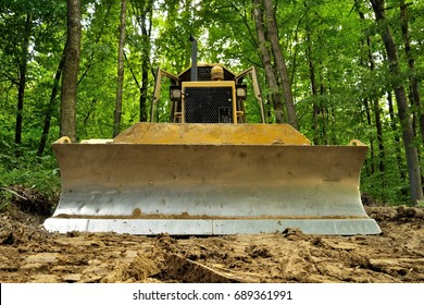 Bulldozer standing in forest for deforestation