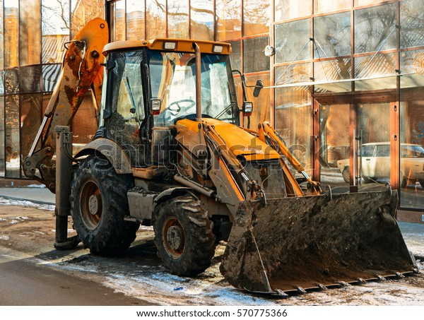 Bulldozer in the street in front of glass wall of modern building Colorized image.