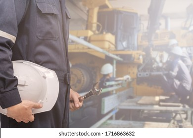 Bulldozer tractor service repair and preventive maintenance, Professional mechanic man with uniform holding safety helmet and spanner tool in construction machinery workshop
