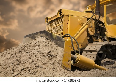 Bulldozer at work on the warm sky background
