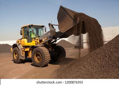 Bulldozer working on manganese in bulk wheel loader
