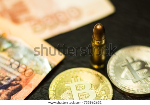 The bullet is among the blurred Russian, Kazakh bills and bitcoins.