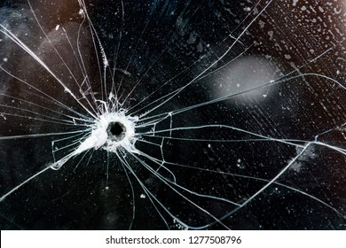 Bullet hole in glass, glass texture with cracks and scratches