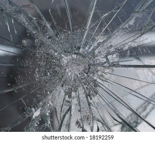 Bullet hole in shattered glass pane
