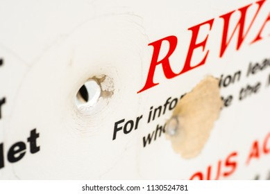Bullet hole through a sign offering reward.
