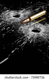 bullet holes in glass with bullet - broken glass isolated on black