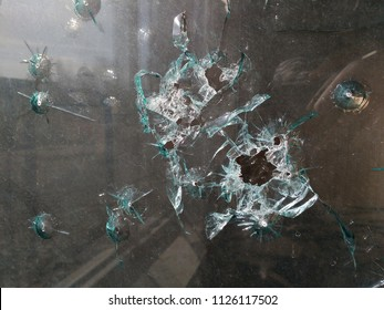 Bullet holes in glass - dangerous neighborhood vandalism.