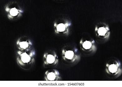 Bullet holes in the metal plate