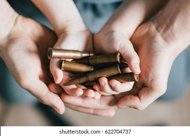 A bullet from the Kalashnikov AK47 assault rifle in the hands of a child and a man. The concept of the war in Syria and North Korea, and the involvement of children in hostilities.