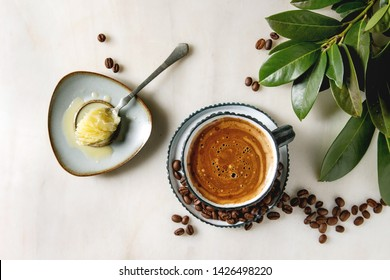 Bulletproof coffee. Keto diet coffee in blue ceramic cup with organic ghee butter in spoon with beans and green branch over white marble background. Flat lay, space