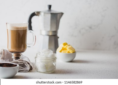 BULLETPROOF COFFEE. Ketogenic keto diet coffe blended with coconut oil and butter. Cup of bulletproof coffee and ingredients on white background. Copy space.