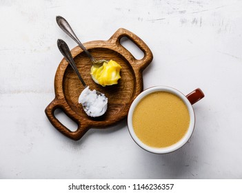 Bulletproof coffee with melted and coconut butter on white wooden background