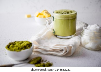 BULLETPROOF MATCHA. Ketogenic keto diet hot drink. Tea matcha blended with coconut oil and butter. Cup of bulletproof matcha and ingredients on white background.
