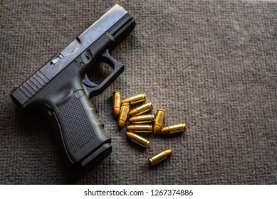 bullets and 9mm gun on black velvet desk