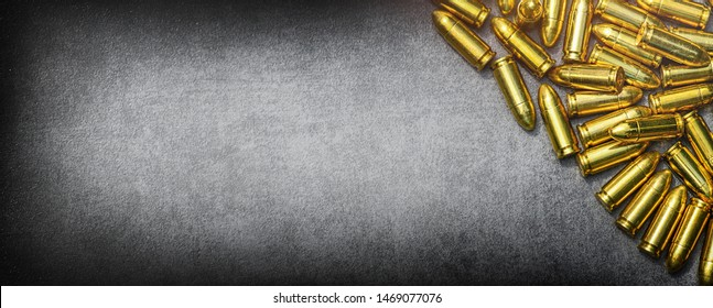 Bullets ammunition on stone table wide banner or panorama. Bullet pile background copy space.  Ammo military technology. Copy space for text photo cocept.