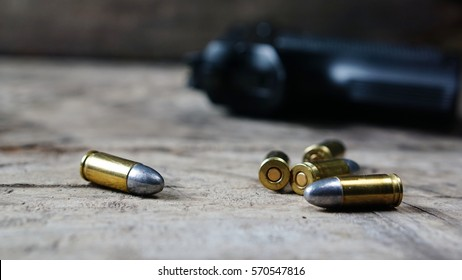 Bullets and a firearm on the wood. Bullets are a projectile expelled from the barrel of a firearm.