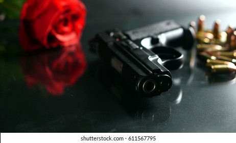 Bullets and a gun on the black mirror floor. Bullets are a projectile expelled from the barrel of a firearm.