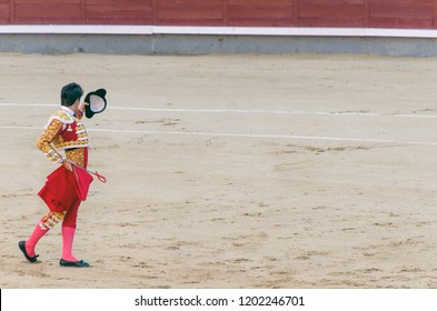 bullfighter with capote and sword raising his montera to greet the public in a bullfighting