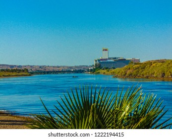 Bullhead City, Arizona / USA - May 11, 2017: View looking south of the Colorado River towards Laughlin Nevada and its casinos, with a palm tree in the foreground and a fishing boat floating down river