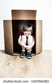 bullied hunched child sitting in a box, seeking for help and refuge from domestic violence in his cardboard home, contrast effects
