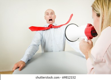 A bullied male worker being blasted by the volume of his boss's megaphone.