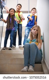 Bullied teenage girl on stairs at school