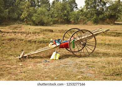 A Bullock cart detached from it's bullocks and kept on a a farm ground with the usable clothes in  bright, tropical winter morning, in an Indian village