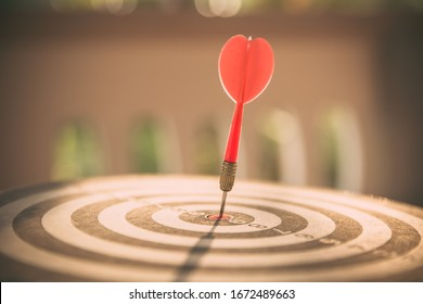 The bullseye, or bull's-eye or dart board has dart arrow hitting the center of a shooting target for business targeting and good success.