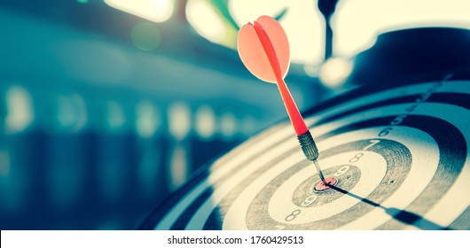 Bullseye or dart board has dart arrow throw hitting the center of a shooting target for business targeting and winning goals business concepts.