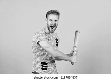Bully man shouting aggressive face, grey background. Man with wooden bat ready to attack. Aggressive behaviour concept. Man bearded looks aggressive and threatening. Dangerous behaviour of hooligan.