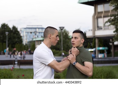 Bullying scene between two adult teenagers in city park.