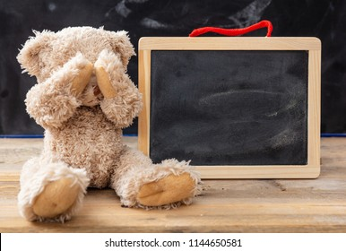 Bullying at school or learning difficulties concept. Teddy bear covering eyes and a blank blackboard, space for text