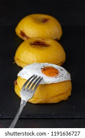 Bulz, a traditional Romanian meal composed of polenta balls stuffed with sheep cheese and roasted smoked sausage, and served with a  soft fried egg.