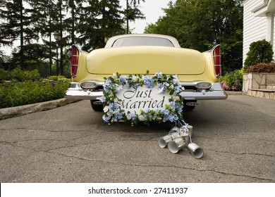 Bumper of limousine with just married sign and cans attached