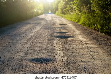Bumpy dirt road with holes against sunshine in background. Shallow field of depth.