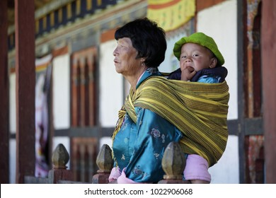 BUMTHANG, BHUTAN - OCTOBER 6, 2011: Mother with baby child on her back in Bhutan.