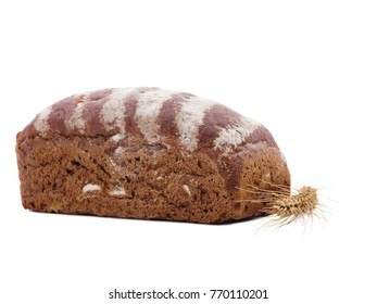 Bun of black bread next to wheat ear on white isolated background