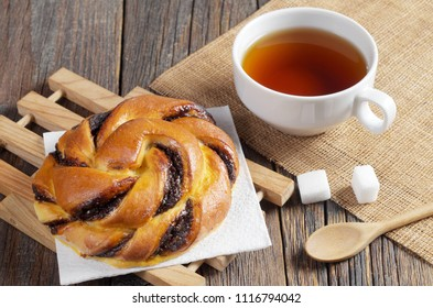 Bun with chocolate cream and cup of tea for breakfast on rustic wooden table close up