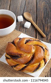 Bun with chocolate cream and cup of tea on old wooden table close up
